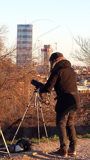 person in brown winter coat taking a photo of a high range building under white sky during daytimr photo