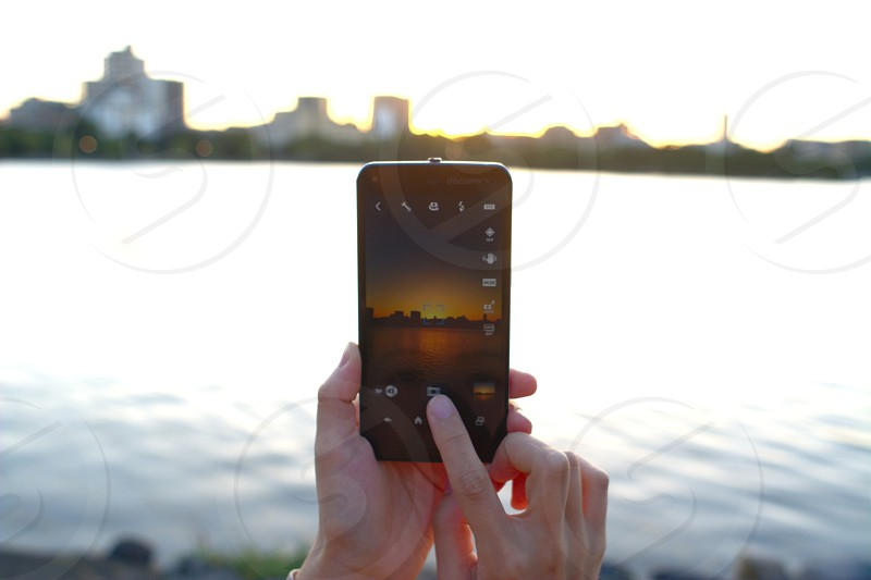 black android smartphone river and high rise buildings photo