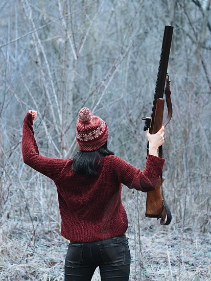 Hunter woman in burgundy warm clothes with gun. Girl hunting in the forest and rejoices her victory by raising rifle up after firing. photo