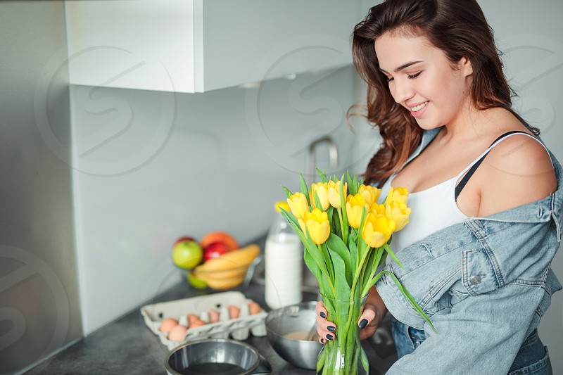Girl holding flowers in the kitchen home with flowers eggs fruits on the table. photo