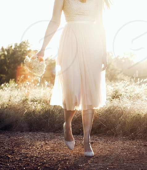 A woman walking while holding a bouquet.  photo