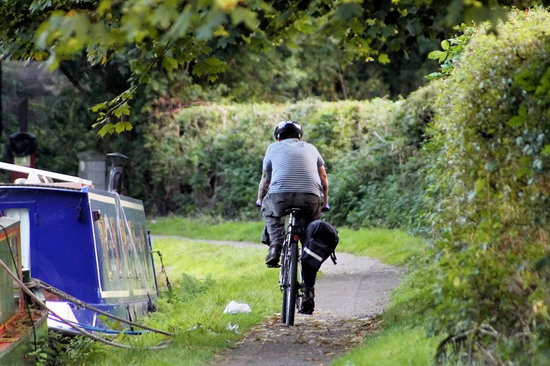 Cyclist on the tow path passing a barge photo