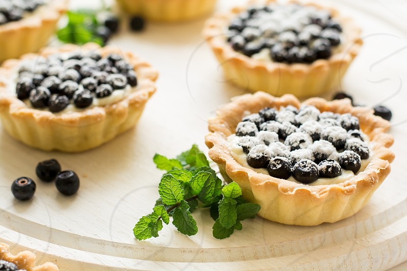 tart fruit fresh freshness closeup crust dessert snack gourmet small tasty confectionery pastry background cooking baked food berry delicious white sweet decorated yummy homemade pie tartlet treat blueberry bakery cream blue cake curd blueberry cake blueberry tart ripe sugar still healthy organic nobody mascarpone baking mint leaves wooden background iced selective focus photo