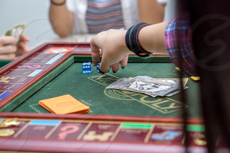 person in pink blue and white plaid elbow sleeve sports shirt leaning forward and putting blue dice on the monopoly game board near other players photo
