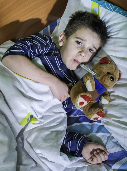 Sick child in bed with teddy bear. Measuring the temperature with a thermometer. photo
