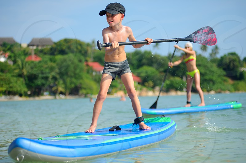 Two kids - boy and girl - having fun on a SUP board. photo