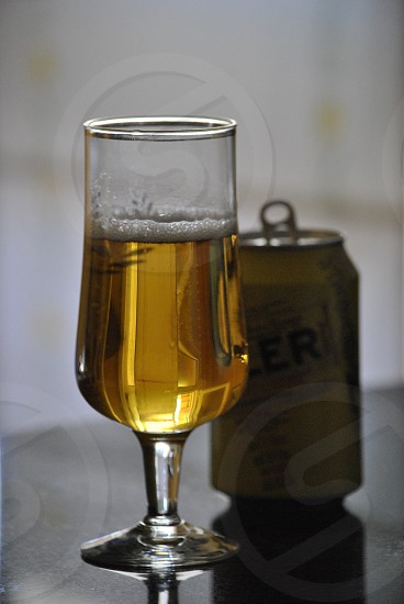 clear drinking glass beside yellow label beer can photo