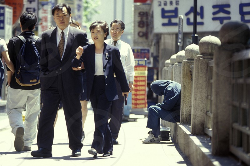poor people at a road in the city of Seoul in South Korea in EastAasia.  Southkorea Seoul May 2006 photo