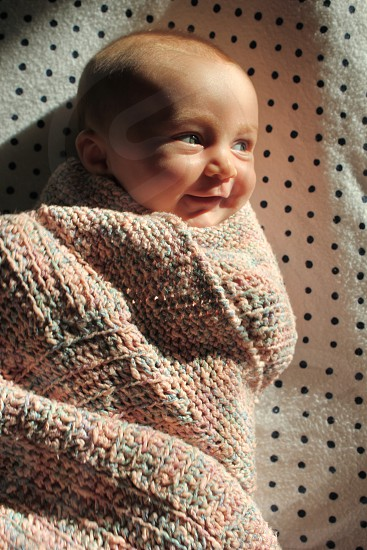 baby with knitted blanket smiling photo