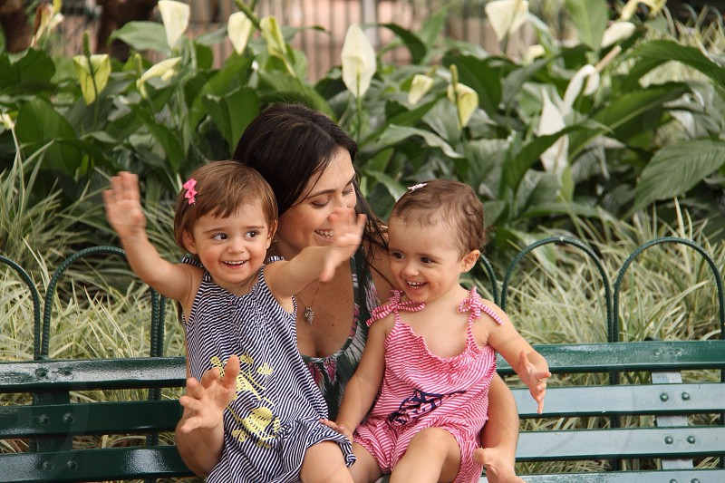woman with two children on bench photo
