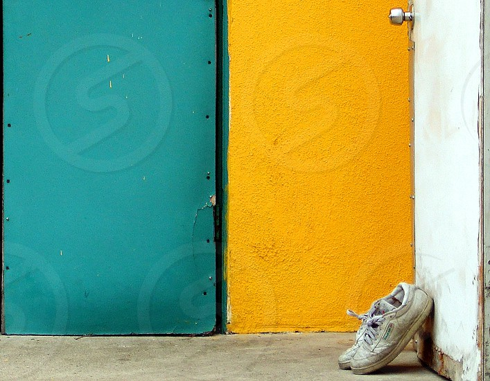 A pair of old sneakers lean against an old door near a yellow wall. photo