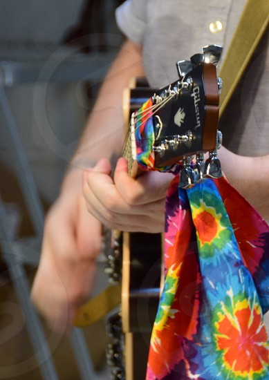 Vibrant colors: Guitar playing with vivid scarf photo