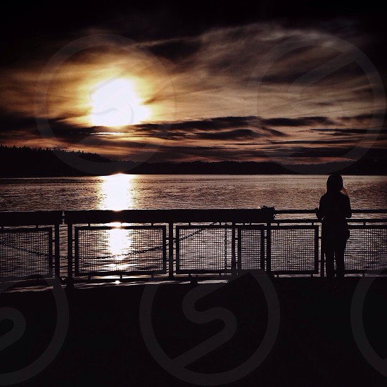 woman at the railing near the water at sunset photo
