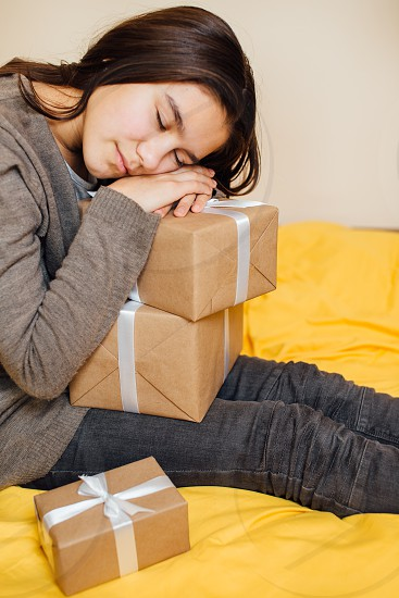 Little girl sleeping on her gifts with closed eyes Christmas time photo