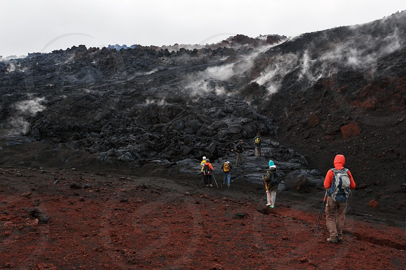 TOLBACHIK VOLCANO KAMCHATKA PENINSULA RUSSIAN FAR EAST - JULY 27 2013: Group of tourists hiking on the lava field eruption Tolbachik Volcano on Kamchatka Region (Klyuchevskaya Group of Volcanoes). photo