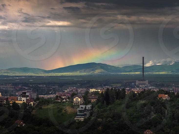 rainbowdramaticeveningduskbrasovromanialandscapetowerskyafter rain photo