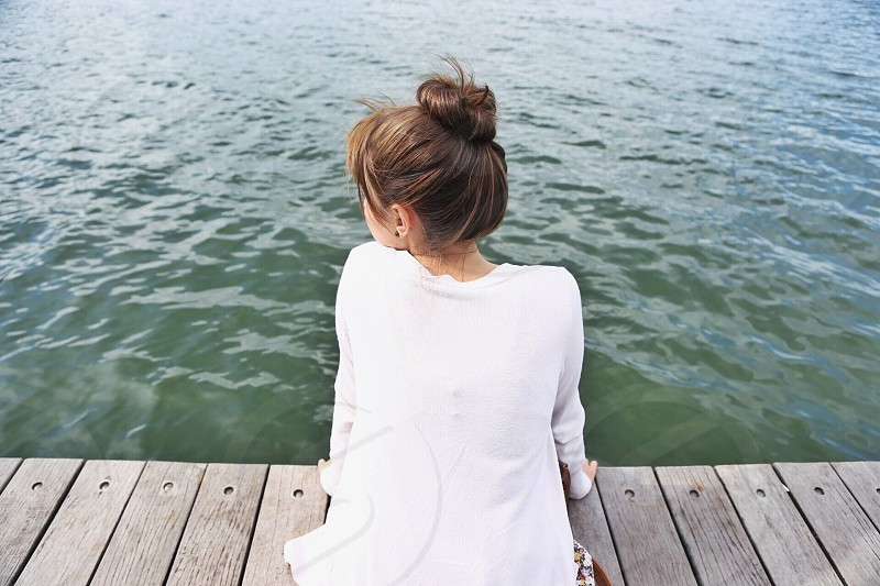 woman wearing white long sleeve crew neck top sitting on brown wooden dock photo