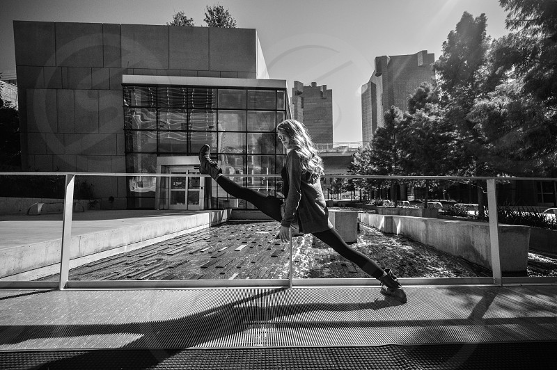 woman taking large steps in front of fountain near modern buildings in black and white photo
