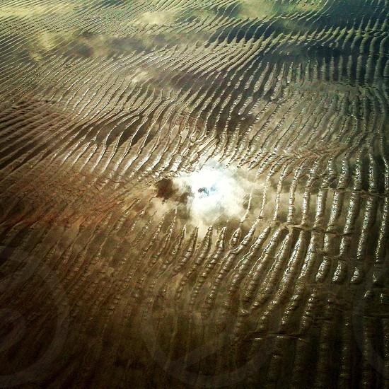 Sunrise reflected in beach sand/water photo