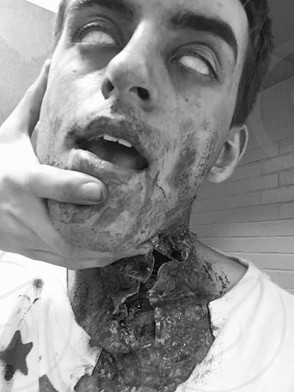 man wearing crew-neck shirt with zombie prosthetics photo