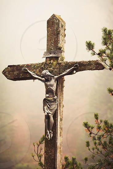 Mobile photography lo-fi styled image of lichens covered figure of Christ on the Cross at the Crucifixion standing outdoors amongst pine branches against a misty fall forest backdrop photo
