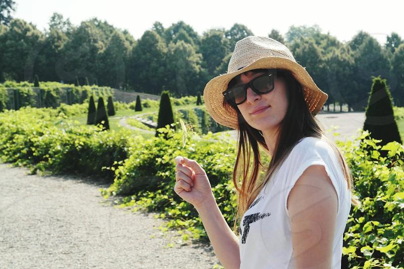 woman portrair hat white green foreat garden walk sunglasses sunshine pathway trees photo