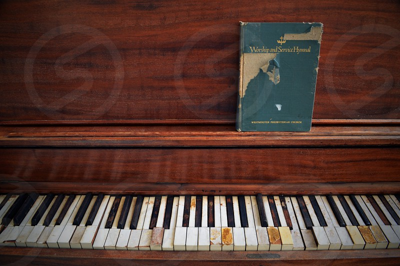 brown upright piano with blue scripted book photo