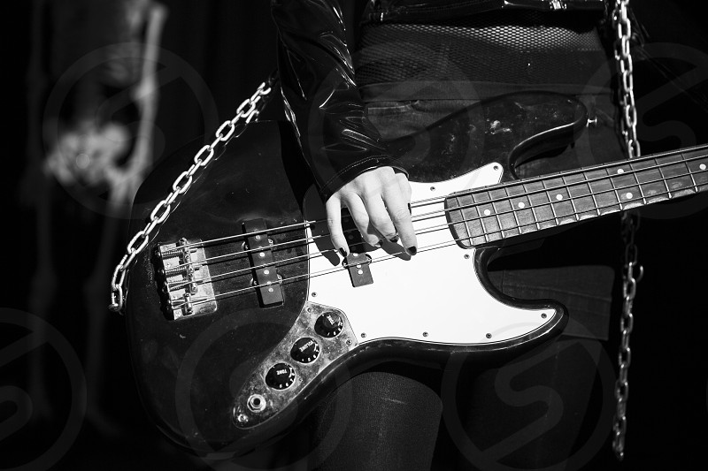 person playing white and gray electric bass photo