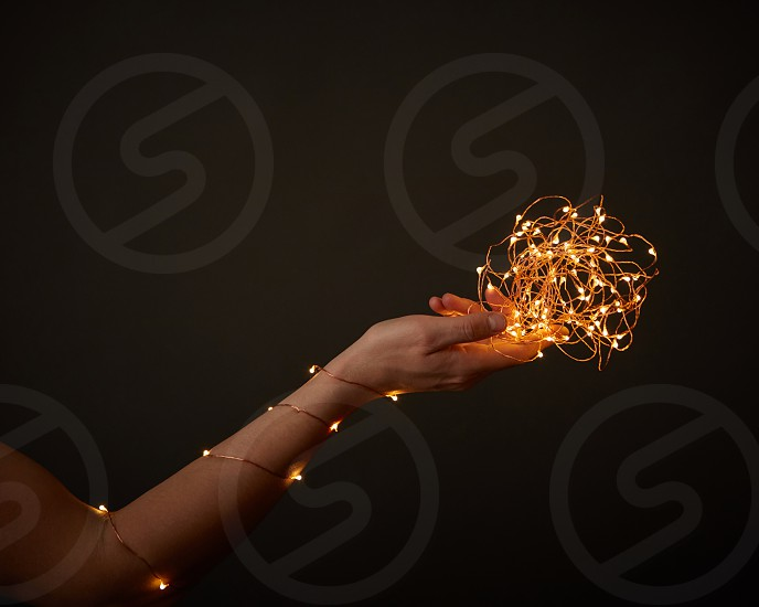 A woman's hand holds bright Christmas lights on a black background with space for text. Creative holiday layout photo