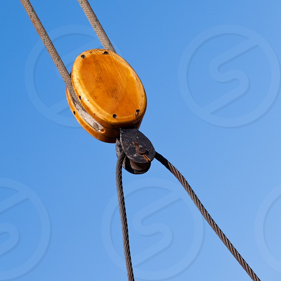 Beautiful wooden cable pulley rigging detail of traditional sail ship yacht against blue sky photo