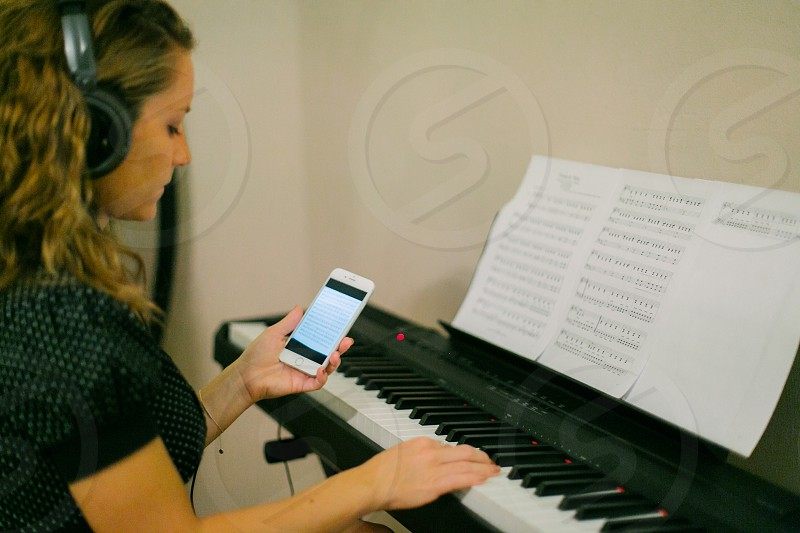 woman in white black blouse using white smartphone and black white piano photo