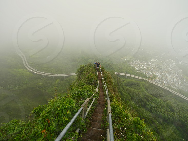 Hikers going up a steep part of staircase on the mountain ridge inside a cloud in Hawaii  photo