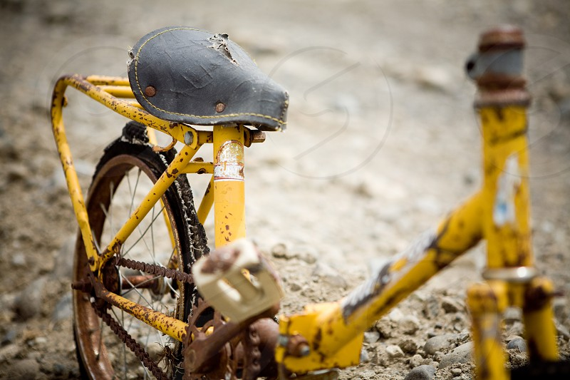 Old yellow child bike dirt road vintage distressed. photo