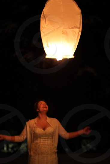 The bride sending off a Chinese lantern into the beautifully dark Alaska sky.  photo