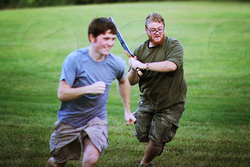 man wearing dark green shirt chasing man wearing blue shirt with bat photo