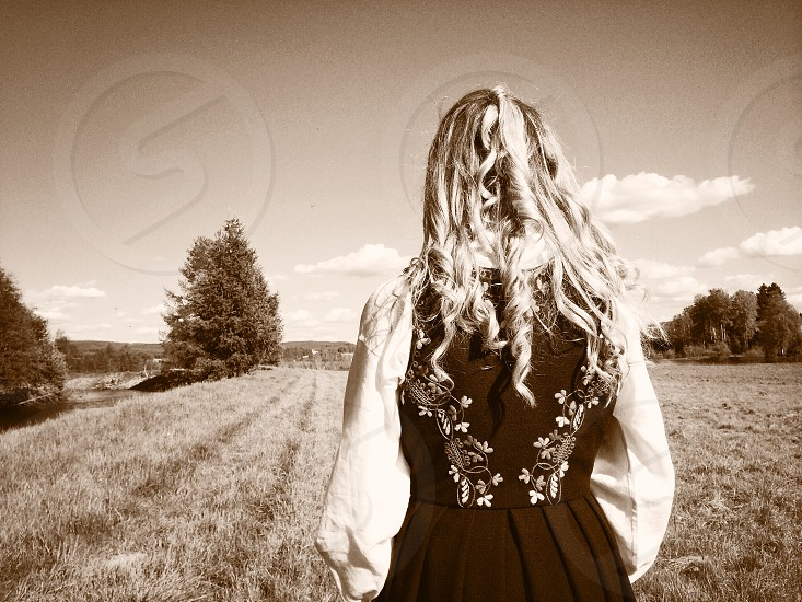 woman in field with curly hair and white shirt under black embroidered jumper photo