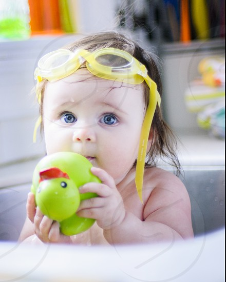 baby in stainless steel sink holding green and red rubber duckie photo