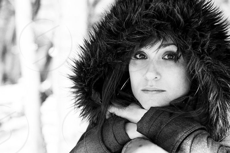 Portrait of a woman with beautiful eyes wearing jacket with fur hood in nature surroundings in winter time photo
