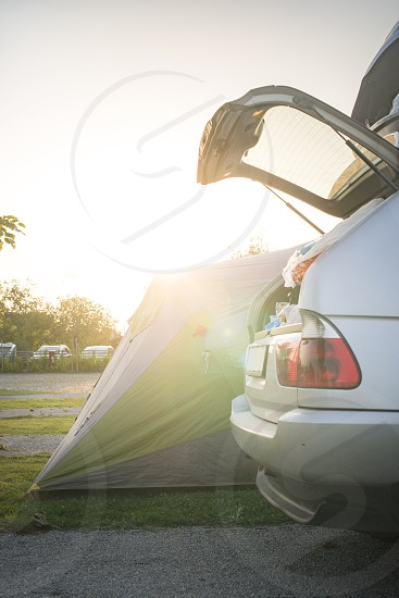 Tent and car on campsite. Sinrise back light photo