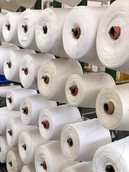 Simple workplace in a weaving factory. Where white thin wrapped sewing threads are transformed into wonderful dresses scarves shorts and much more. From a series of unique photos. photo