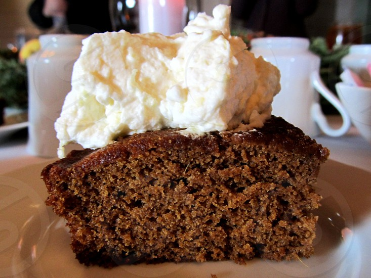 Slice of gingerbread topped with hand-whipped cream photo