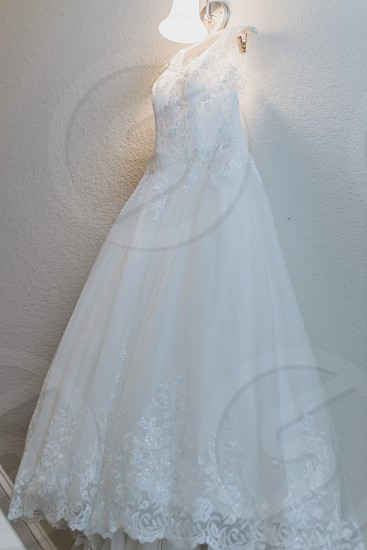 White wedding gown hanging on wall under warm light photo
