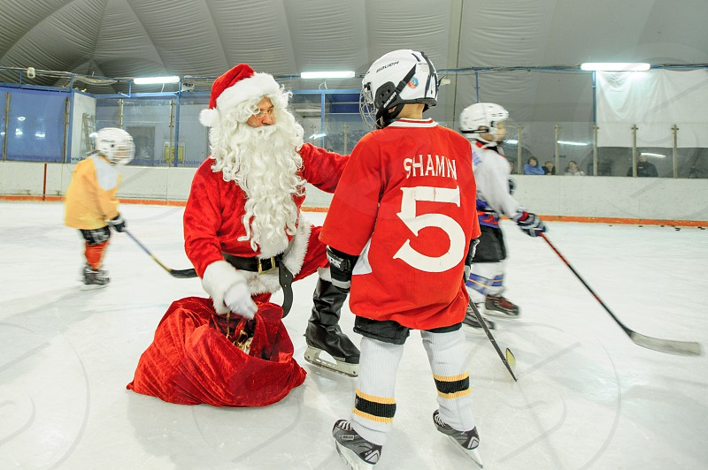 Ice skating with Santa Claus: little ice hockey players receiving Christmas gifts photo