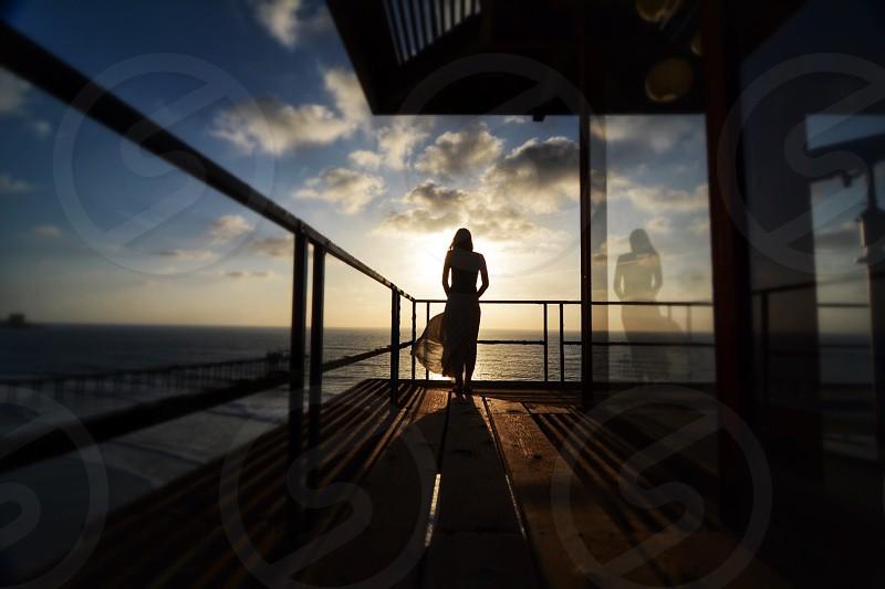 woman standing on veranda overlooking the sea photo