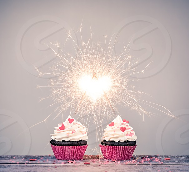 Two valentines day buttercream Cupcakes with sparklers creating a heart shape celebrating love concept photo