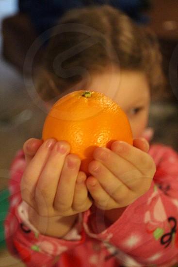 Child in pajamas holding orange in both hands photo