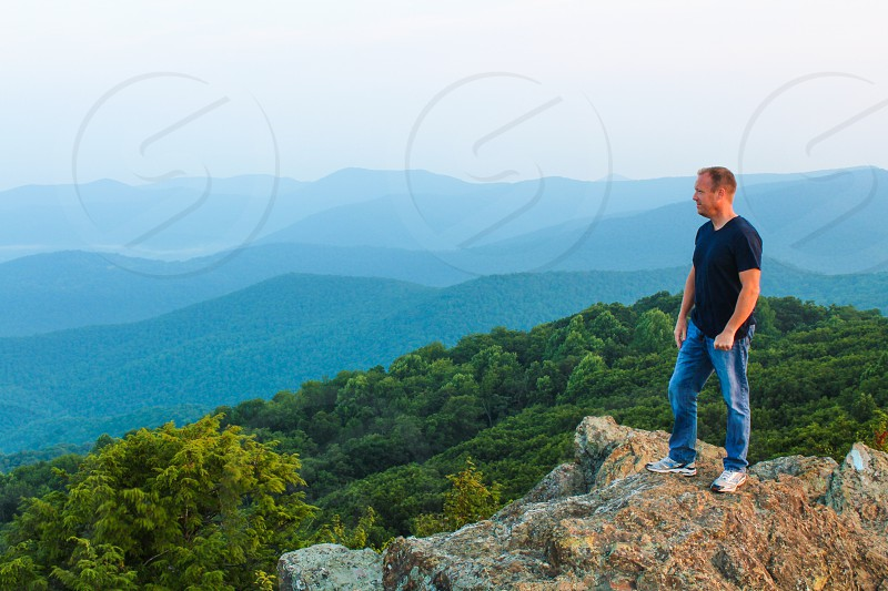 man wearing blue denim jeans standing on mountain cliff facing forest during day photo