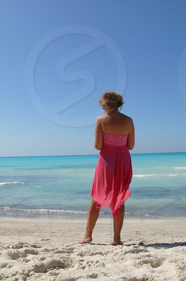 beach white sand pink dress woman reading photo