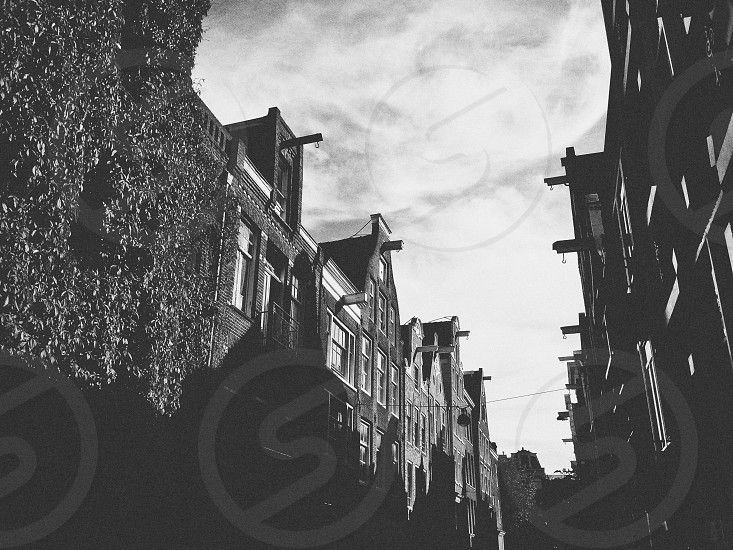 buildings under white clouds gray scale photo photo