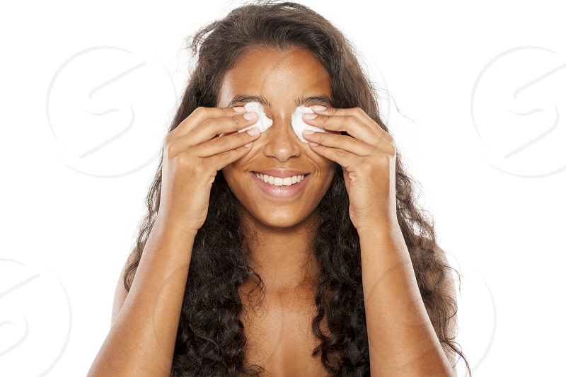 Beautiful dark skinned girl cleans her face with a cotton pad photo